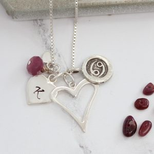 Silver heart necklace personalised with an initial charm, ruby birthstone and Cancer charm